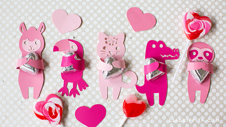 pink animal candy huggers with paper hearts and candy on grey and white polka-dot background