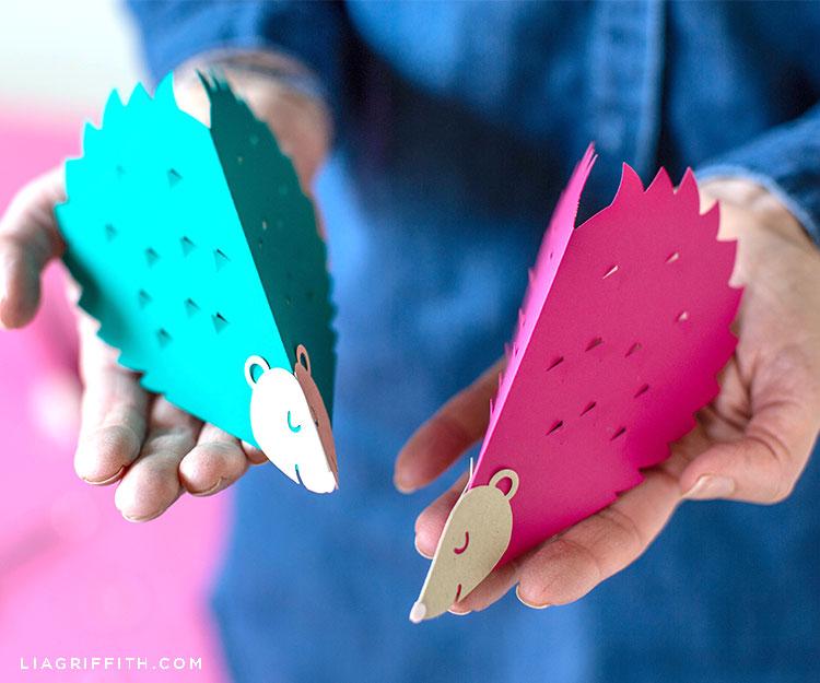 Person holding papercut hedgehog valentines