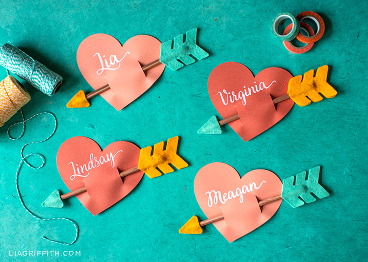 paper heart and felt pencil arrow valentines on turquoise background with rolls of tape and twine