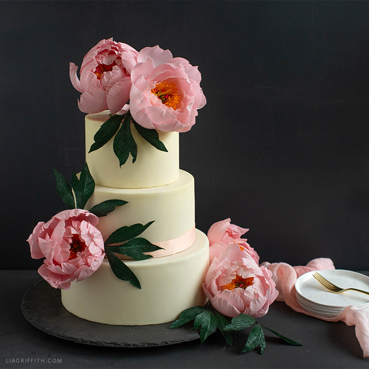 crepe paper coral supreme peony flowers on cake next to plates