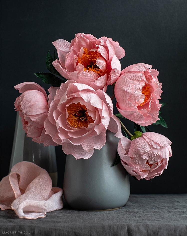 crepe paper coral supreme peony flowers in grey vase