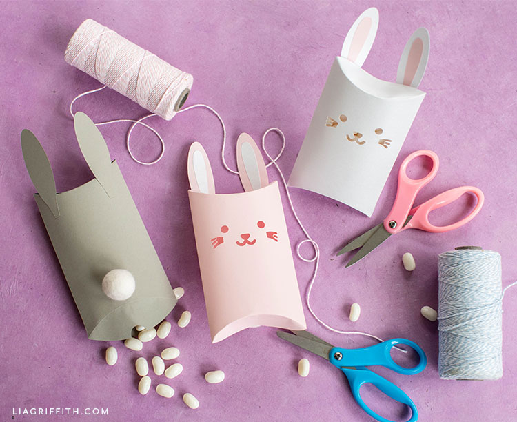 papercut bunny pillow box in pink, grey, and white with thread, scissors, and candy