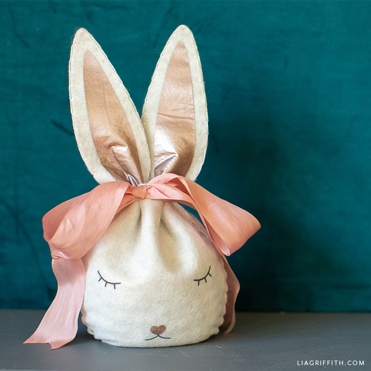 felt Easter bunny treat bag with pink ribbon against teal wall