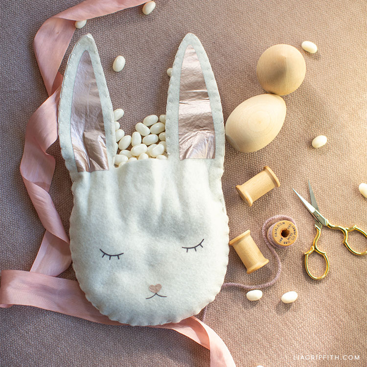 felt Easter bunny treat bag filled with candy next to pink ribbon, wooden eggs, scissors, and spools