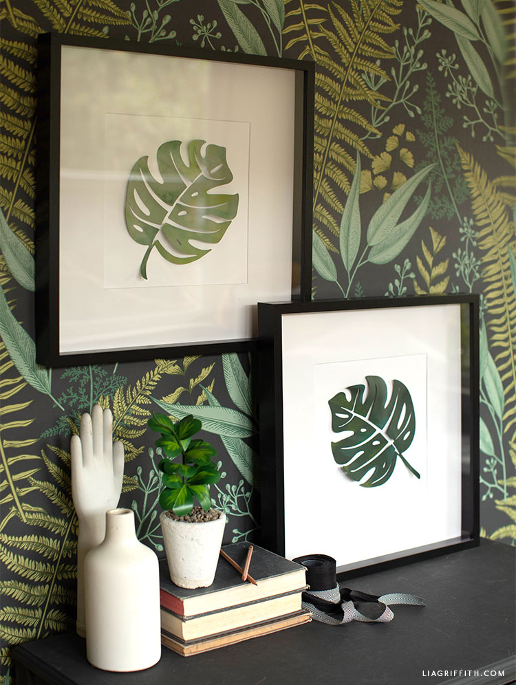 painted monstera leaf artwork hanging on wall with leaf print next to potted paper plant and hand décor
