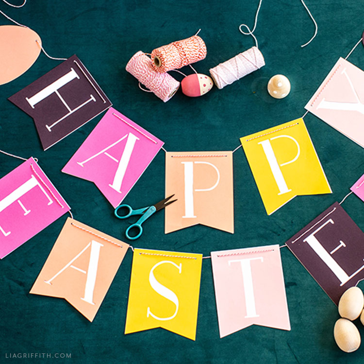 papercut Happy Easter banner on teal background with scissors, wooden eggs, and spools of thread
