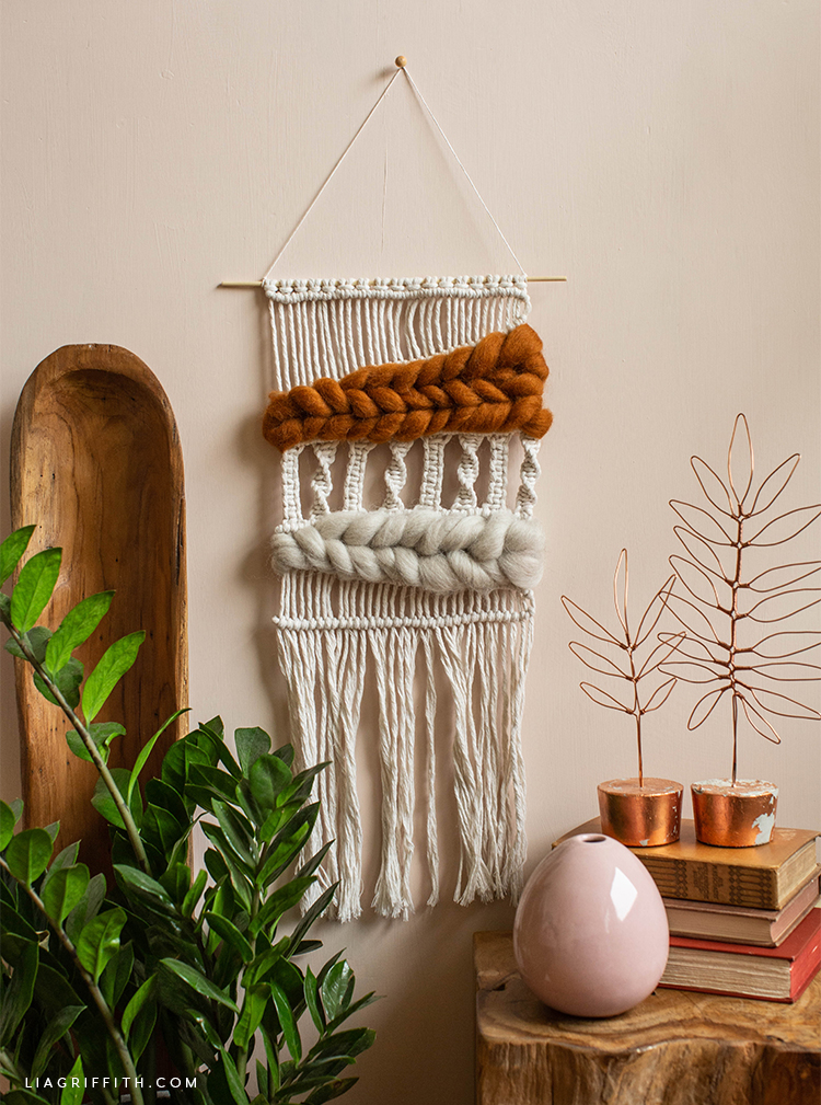 macramé and woven wool wall hanging next to wooden tray, copper wire leaf décor, and plant