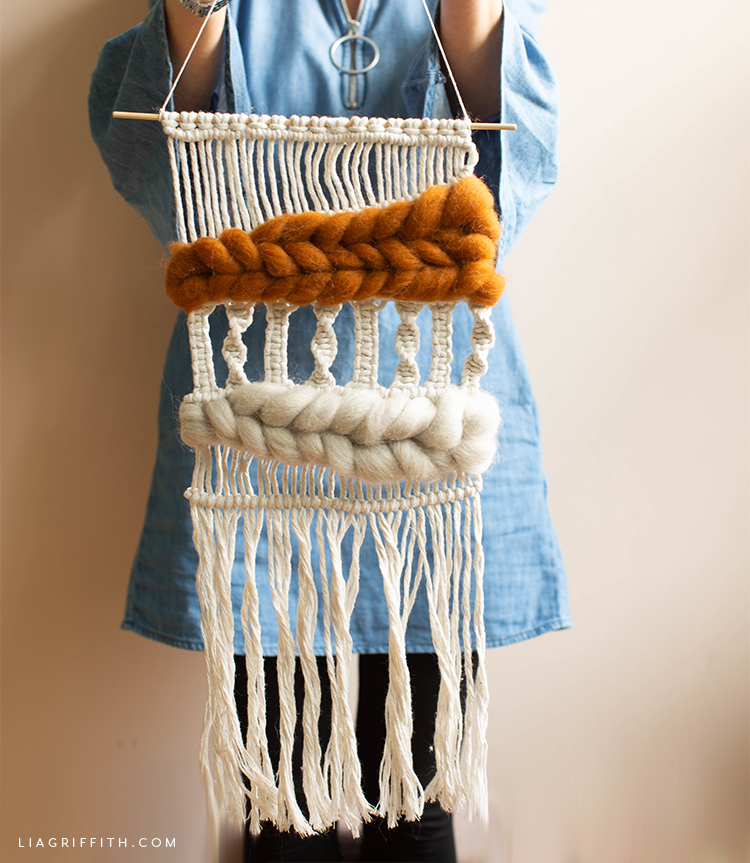 Person holding macramé and woven wool wall hanging