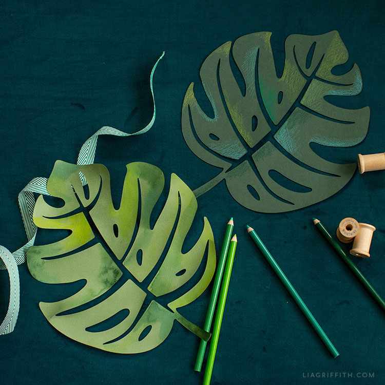 painted monstera leaves next to green colored pencils, green ribbon, and spools