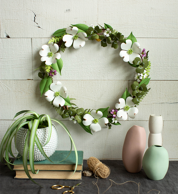 paper shamrock and dogwood wreath on white wall above paper plant, vases, and books