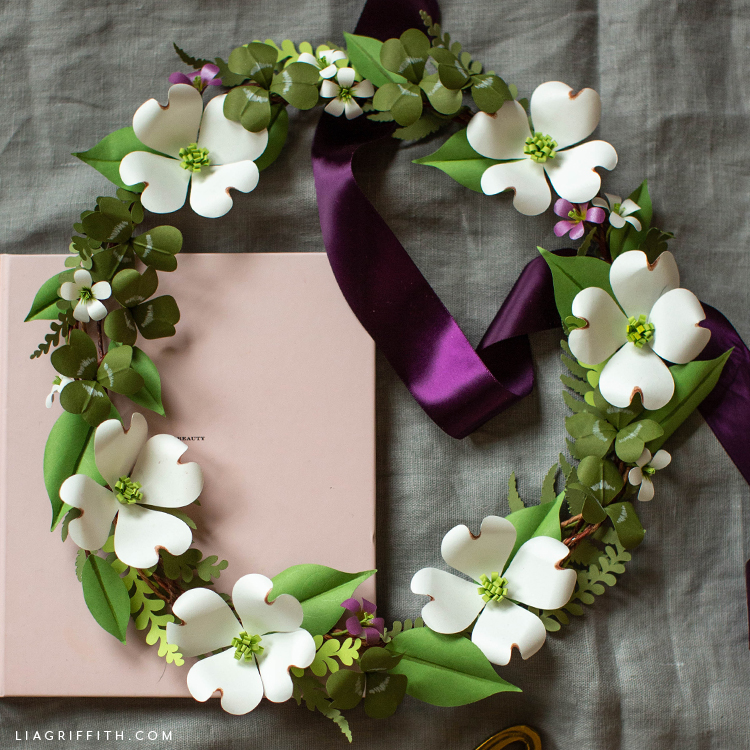 paper shamrock and dogwood wreath with purple ribbon and pink book on grey sheet