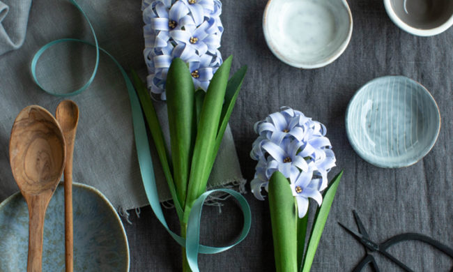 frosted paper hyacinth flowers next to small bowls and wooden spoons