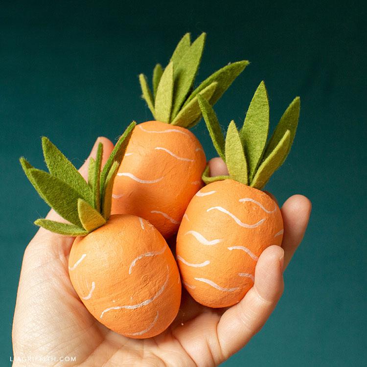 hand holding carrot Easter eggs