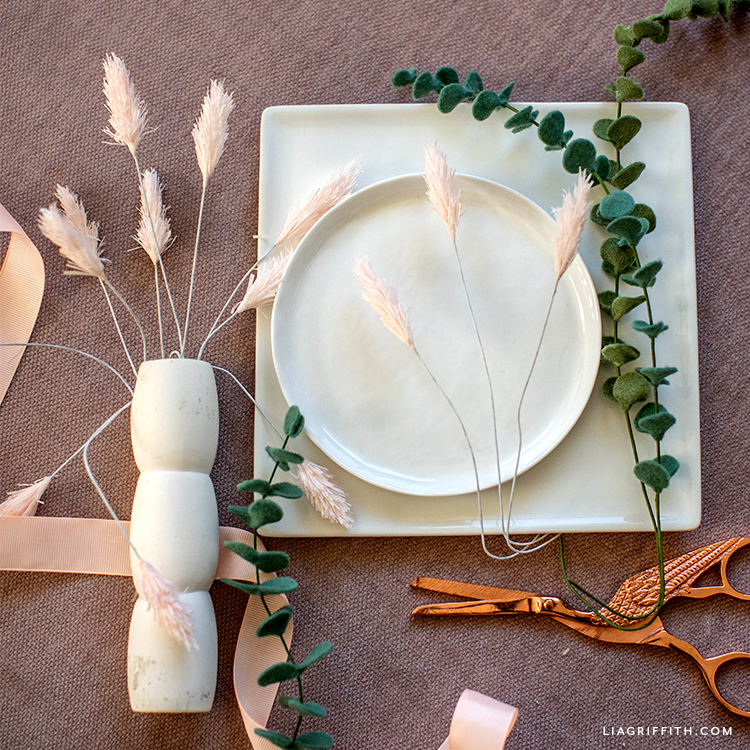 pink crepe paper bunny tails in white vase and on white plate next to felt eucalyptus