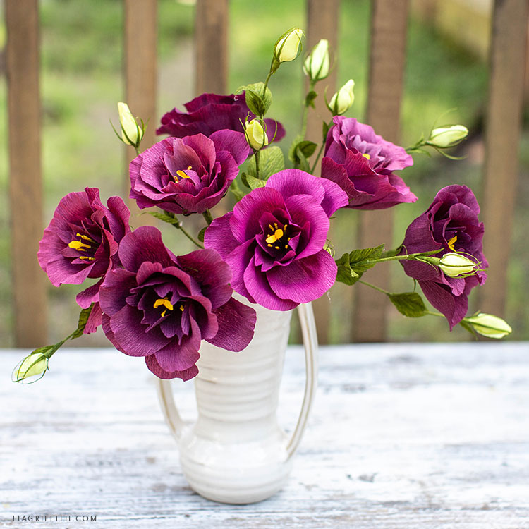 purple crepe paper lisianthus flowers in white vase on white bench outside