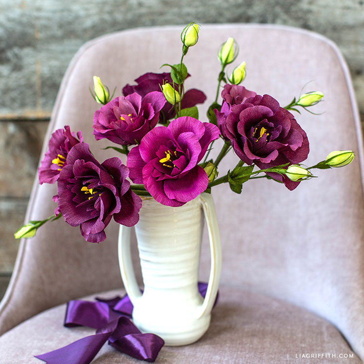crepe paper lisianthus flowers in white vase on chair