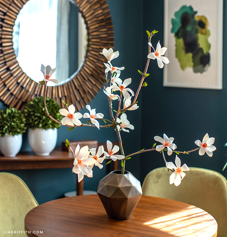 crepe paper tulip magnolia branch in vase on table in front of mirror