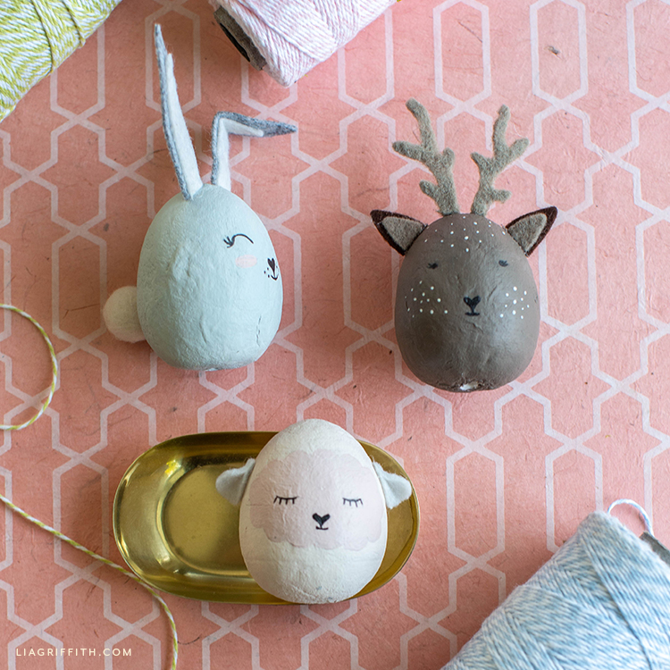 painted animal Easter eggs on pink and white background with twine