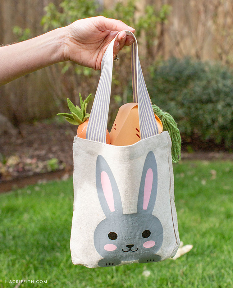 Person holding Easter tote bag with paper and felt carrots in backyard