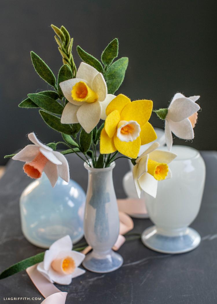 felt daffodils in narrow vase next to empty vases