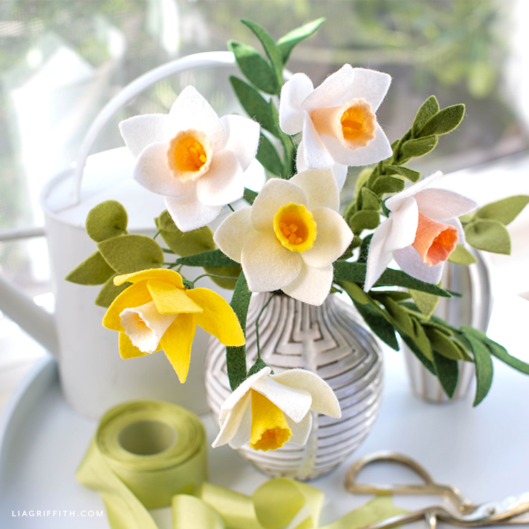 felt daffodils in vase next to watering can, green ribbon, and gold scissors