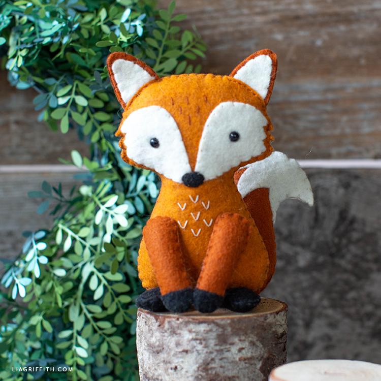 felt red fox stuffie sitting on little stump in front of paper wreath