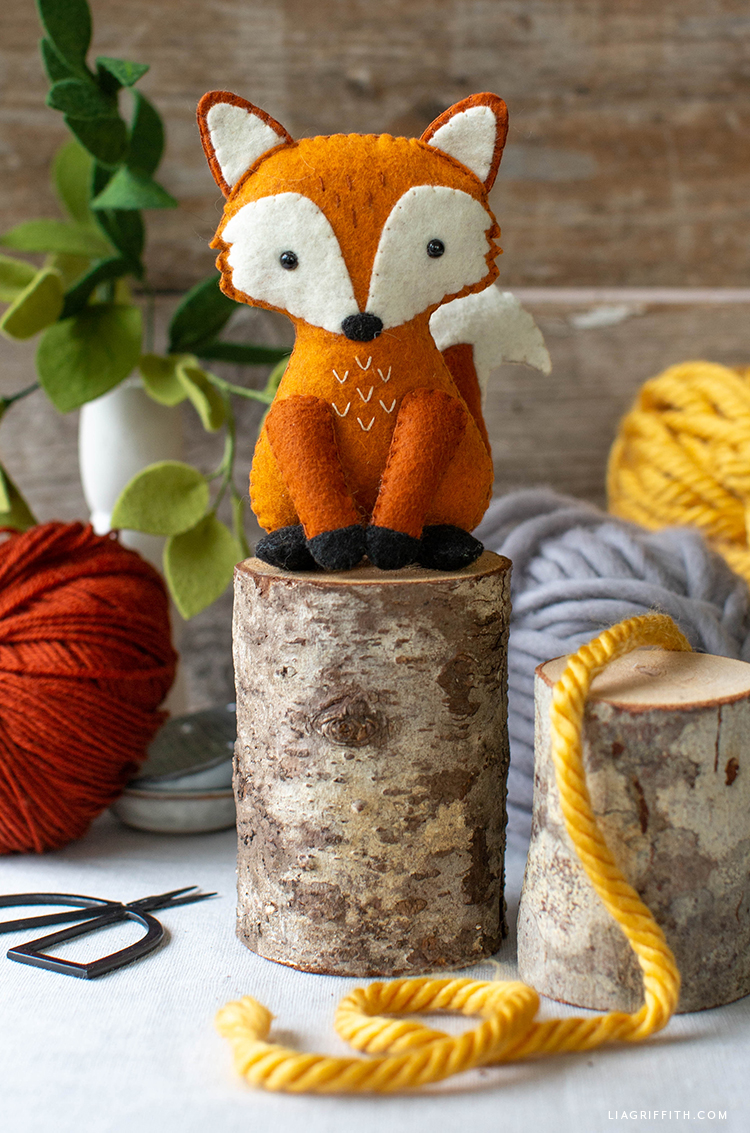 felt red fox stuffie on little tree stump with yarn and felt greenery in background