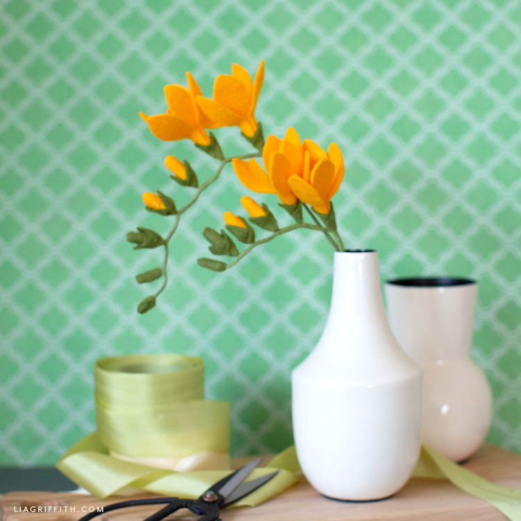 felt freesia flowers and buds on stem in white vase next to empty vase and green ribbon