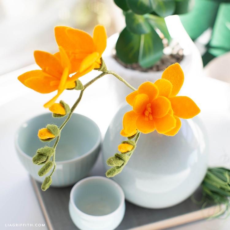 felt freesia flowers in white vase on tray with white bowls