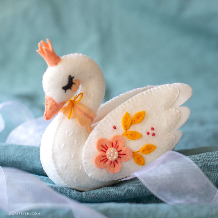 felt swan stuffie on turquoise sheet with pale ribbon