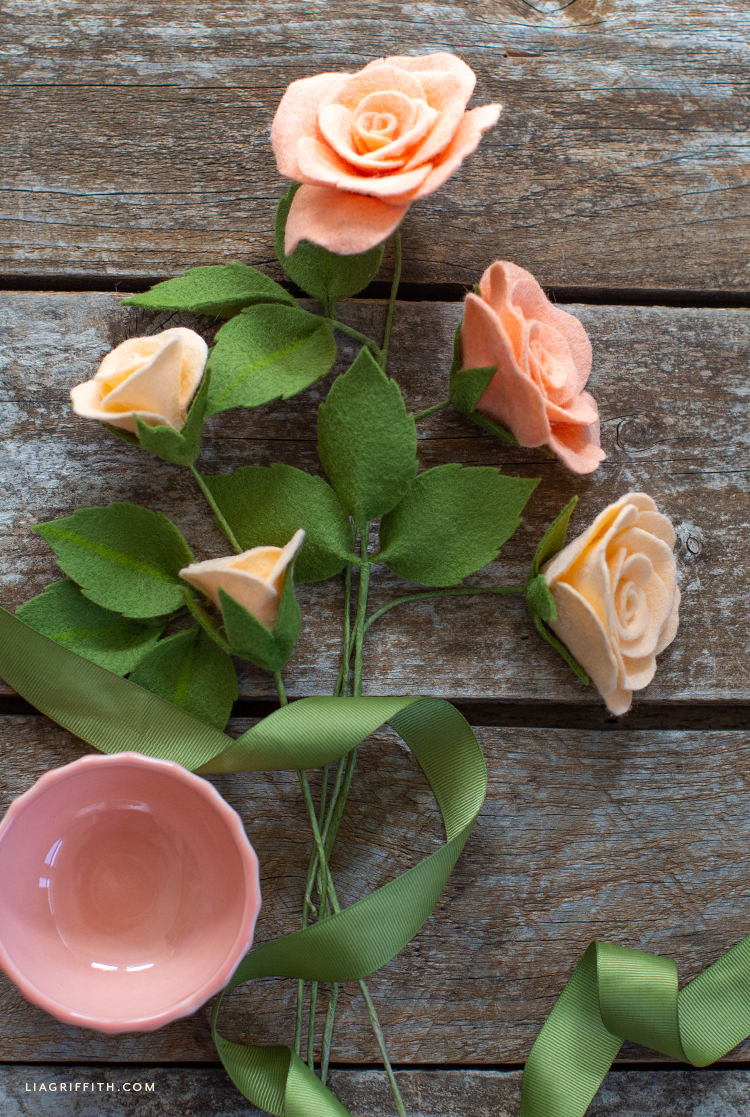 felt tea roses and buds with leaves on wooden table with pink cup