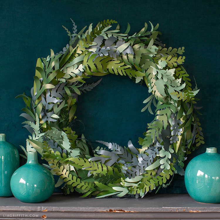 frosted paper fern and eucalyptus wreath next to turquoise vases