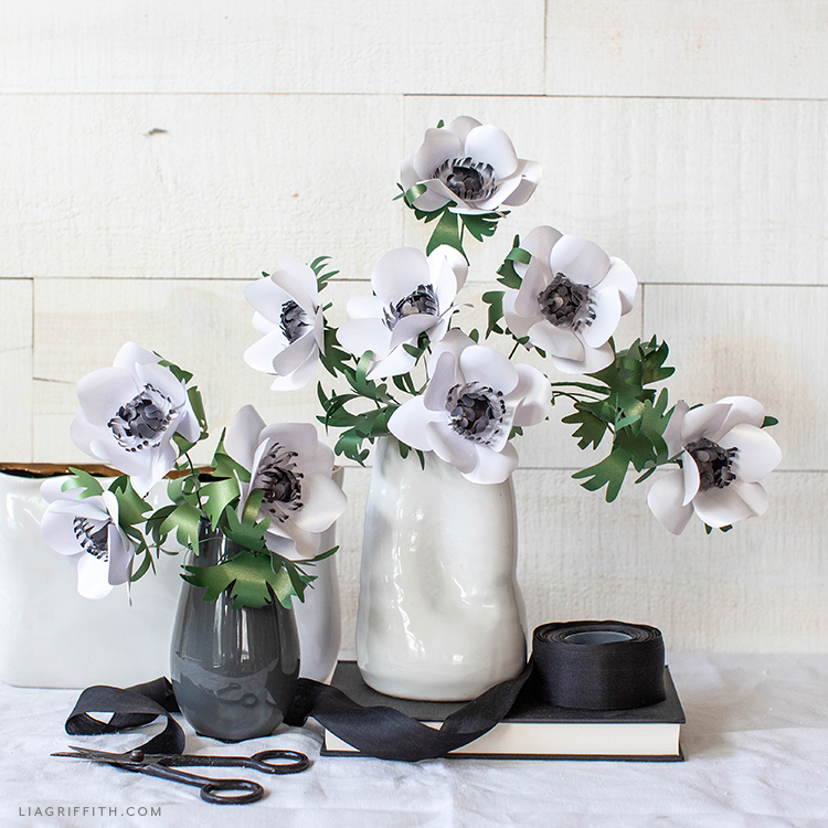 black and white frosted paper anemones in black and white vases on book with black ribbon and black scissors