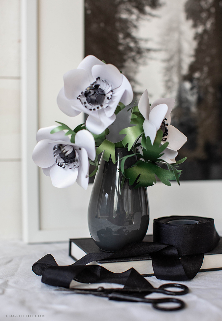 black and white frosted paper anemones in black base on black book next to black ribbon
