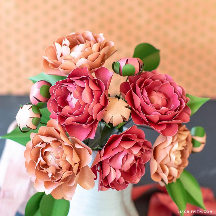 frosted paper camellia flowers in white vase against orange polka-dot background