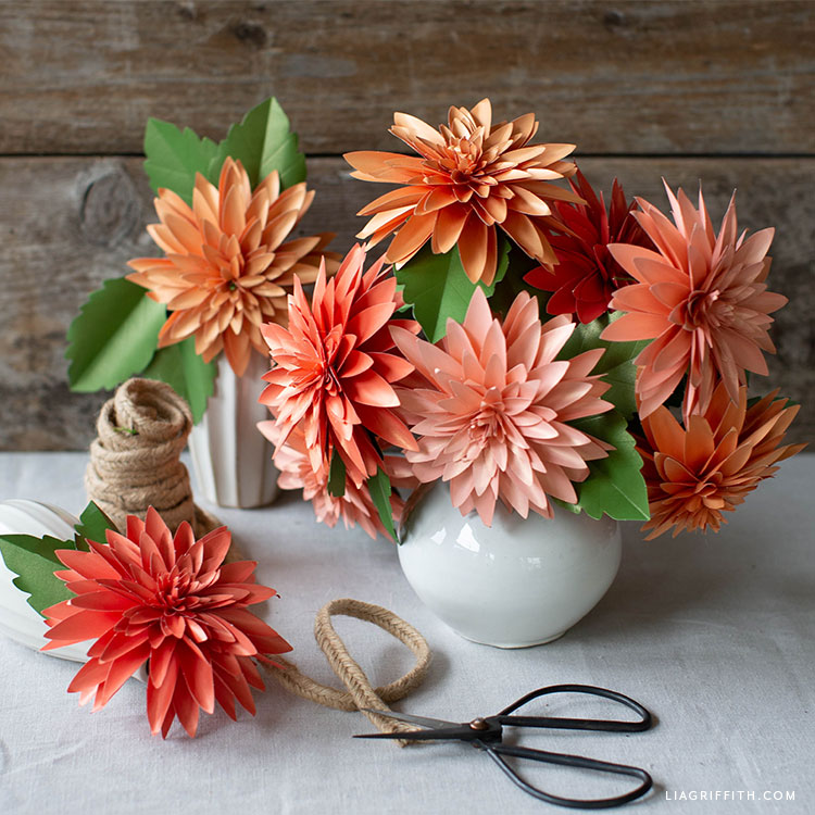 frosted paper dahlia flowers and leaves in vase next to scissors