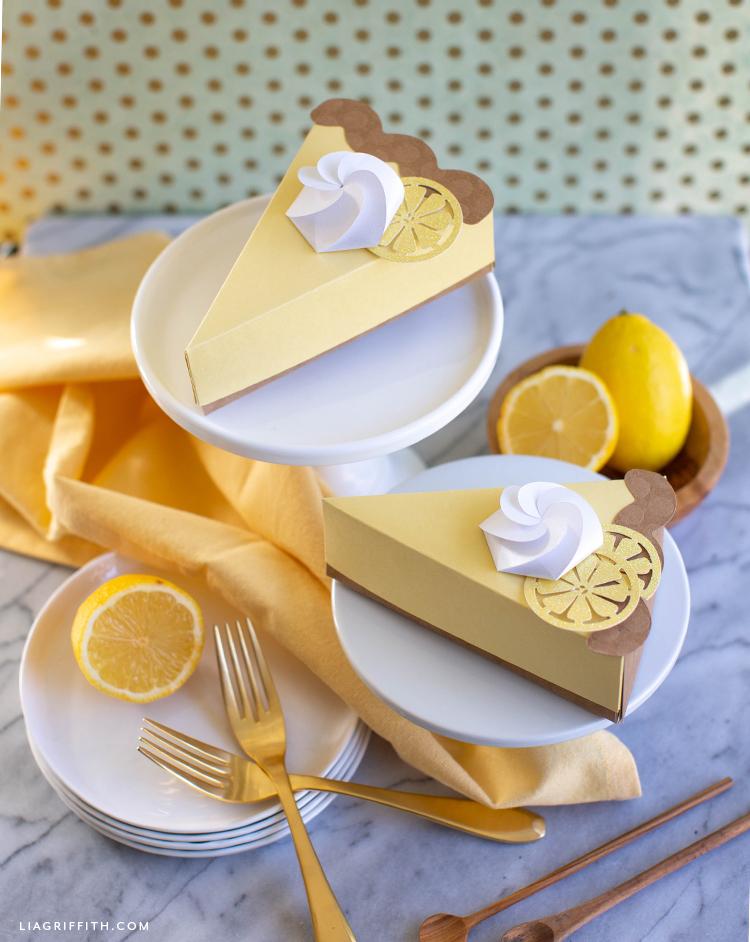 paper lemon tart pie boxes on plates next to forks and lemons