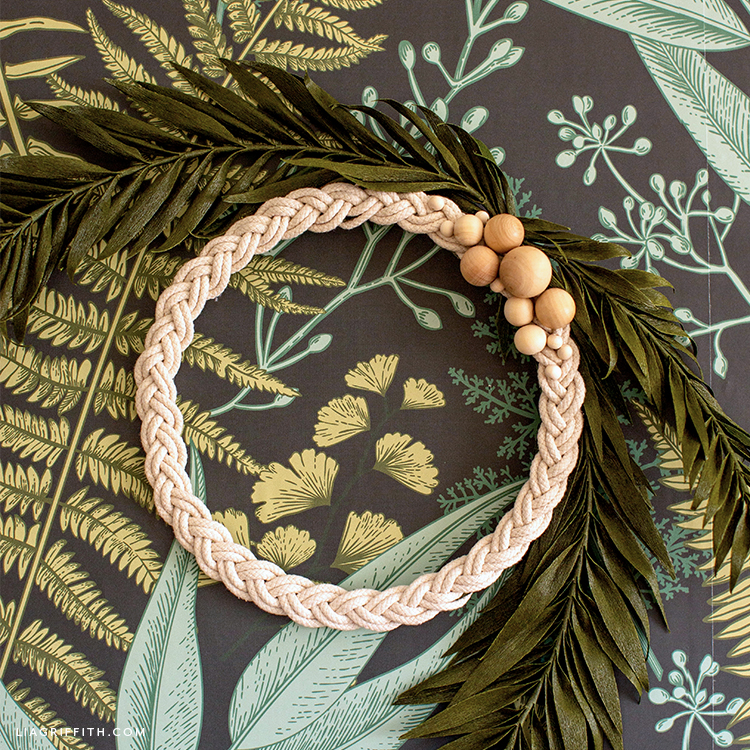 braided rope wreath with wooden beads and crepe paper palm fronds on botanical wallpaper