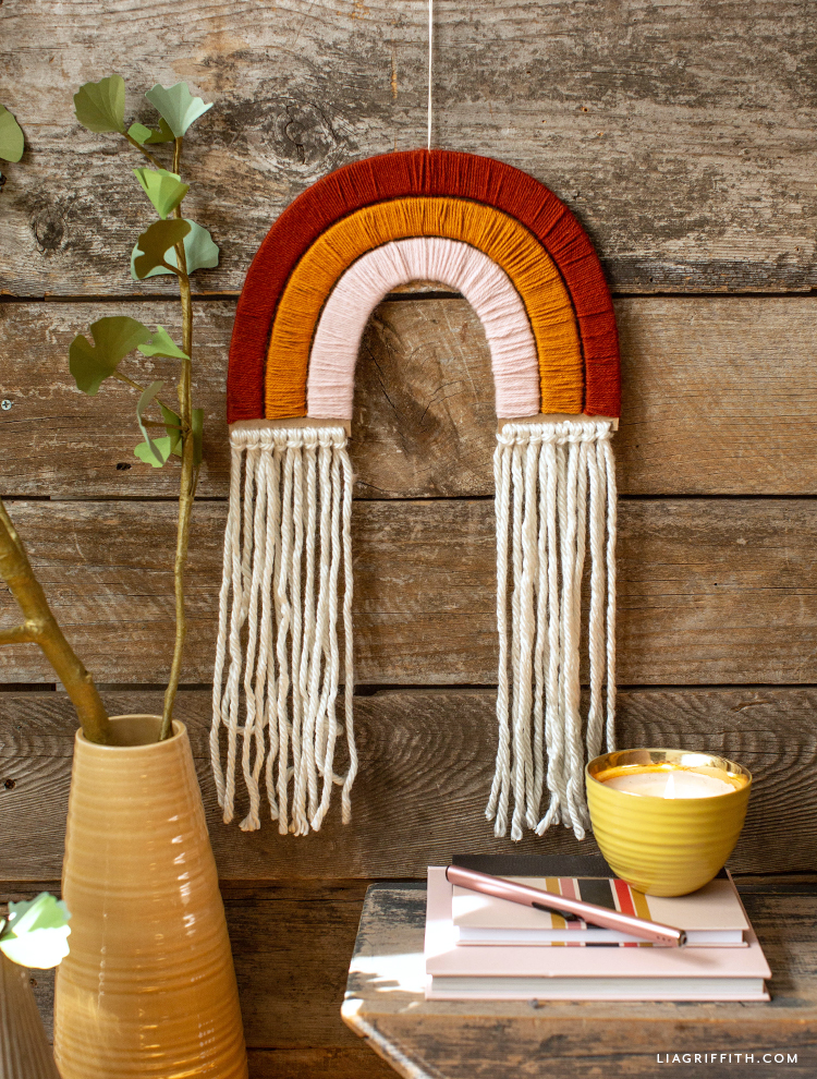 yarn-wrapped rainbow wall hanging on wood slats next to yellow vase with branch