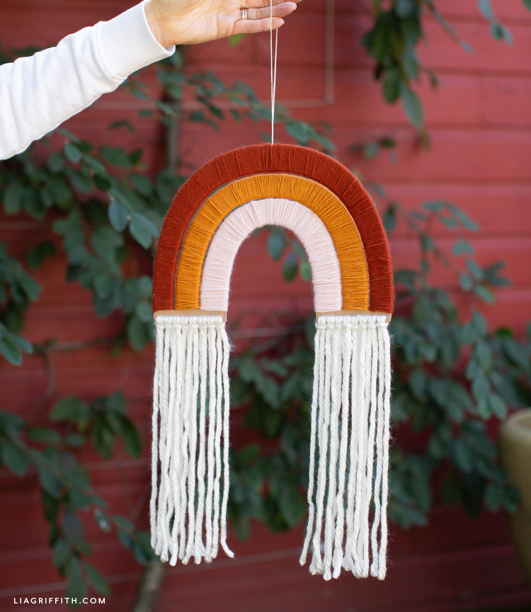 person holding yarn-wrapped rainbow wall hanging outside in front of plant