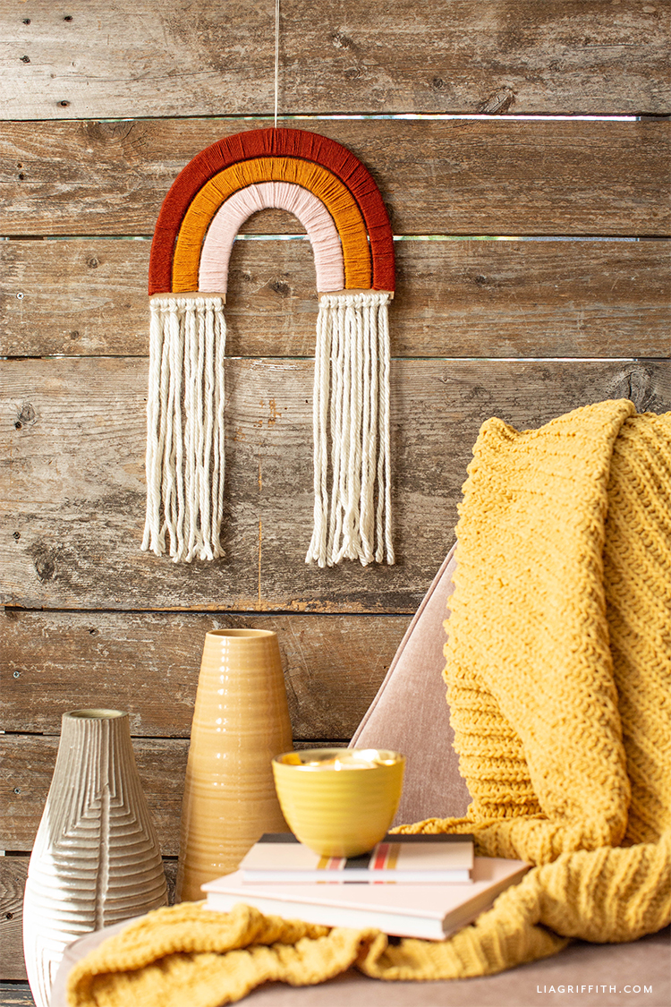 yarn-wrapped rainbow wall hanging on wood wall above chair with yellow blanket and yellow vases