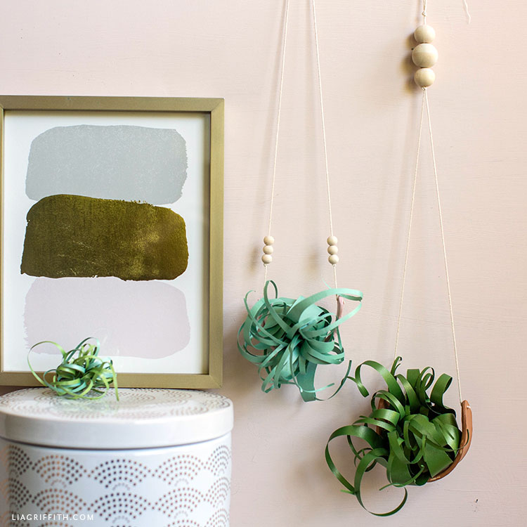air plant holders with paper air plants on wall next to framed artwork