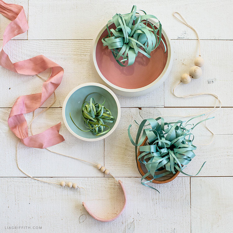 paper air plants in bowls next to pink ribbon and beaded string