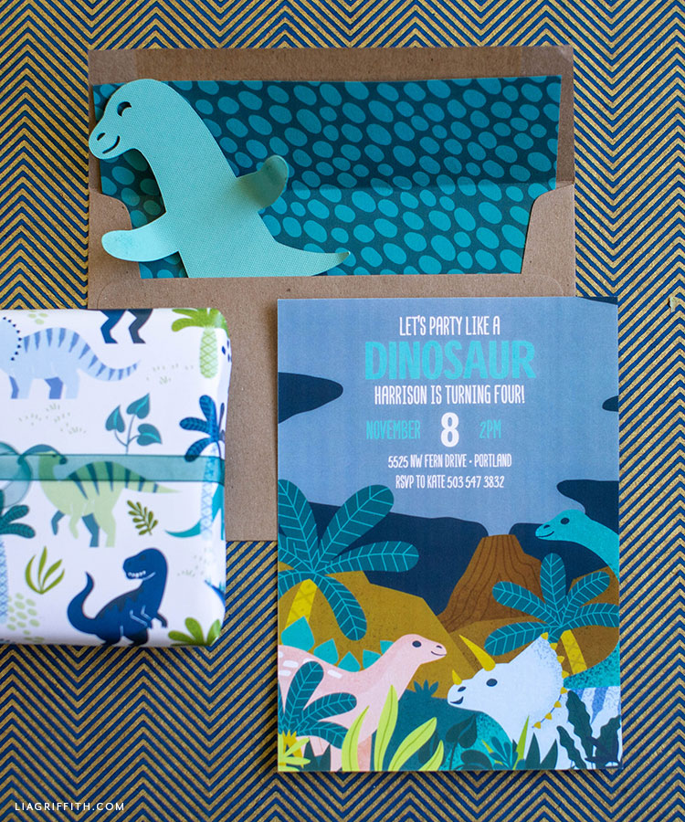 dinosaur party invitation with dino gift wrap and paper dinosaur in envelope