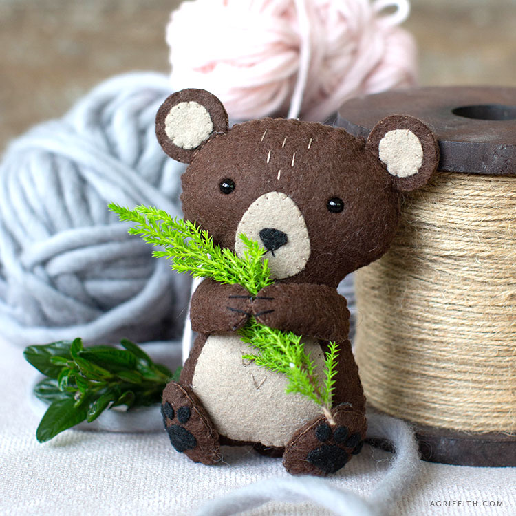 felt brown bear stuffie holding pine tree sprig next to spool of twine and yarn