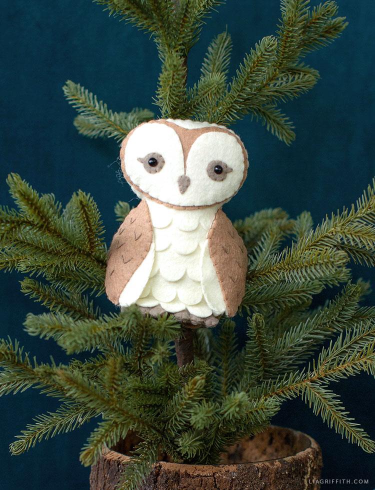 felt barn owl stuffie sitting in little pine tree