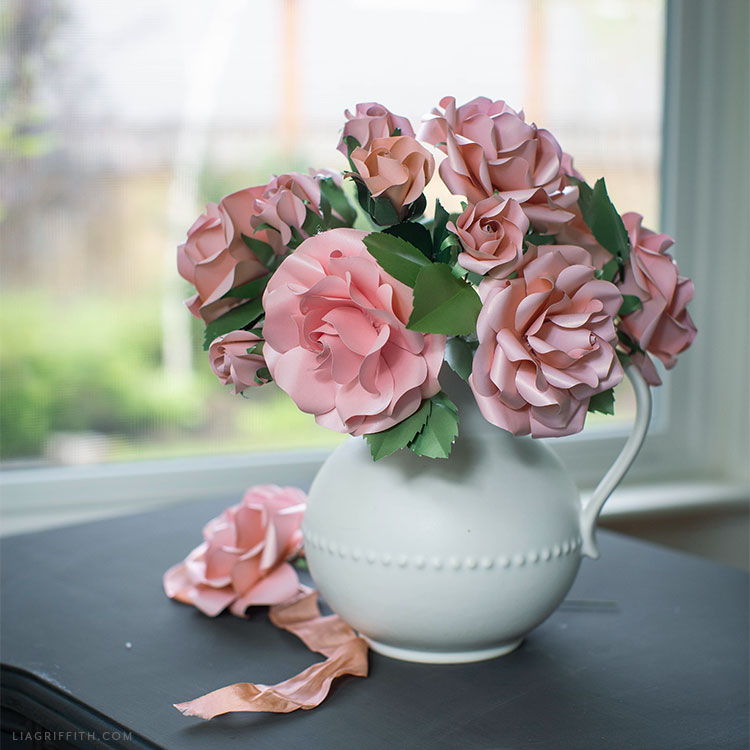 pink frosted paper garden roses and buds in white vase near window