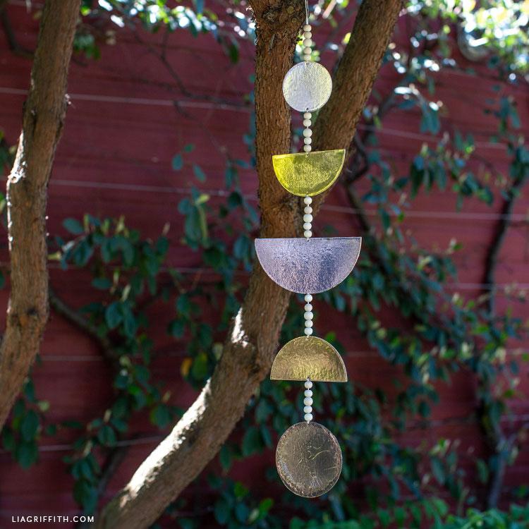 geometric wall hanging on tree outside