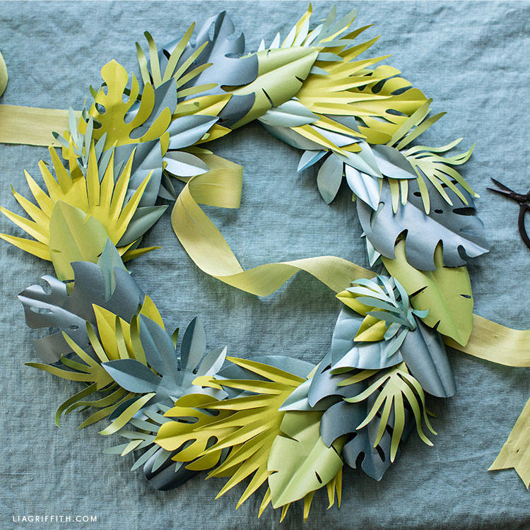 frosted paper tropical wreath with green ribbon on turquoise sheet