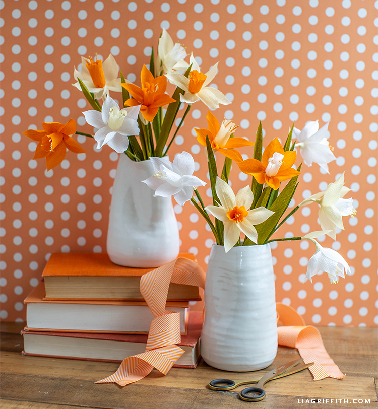 crepe paper flower bouquet in vase on stacked books